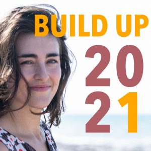 a smiling woman on a beach with the words Build Up 2021